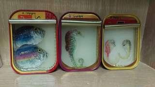 Painted fish and seahorse in tins by French artist Otaire de Coupigny