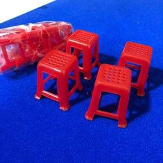 Miniature plastic red stools / chairs