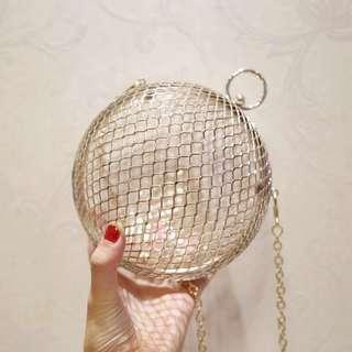 Round cage gold clutch bag