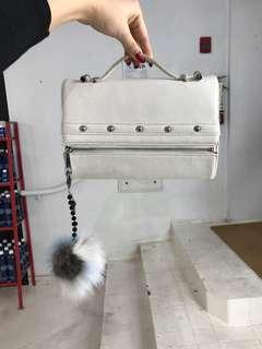White zip clutch with pom pom chain