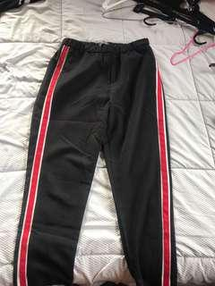Black pants with red and white on the sides