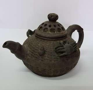 Giant antique rustic teapot decorated with crabs