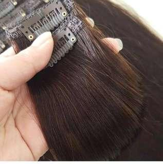 Clip in human hair extensions in dark brown