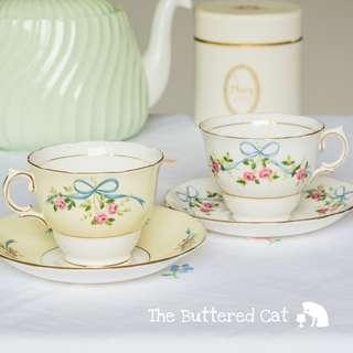 TWO pretty vintage English bone china teacups and saucers, blue ribbon bows and pink roses