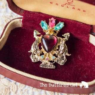 Regal vintage crest brooch with pink and blue rhinestones and a purple-red heart cabochon