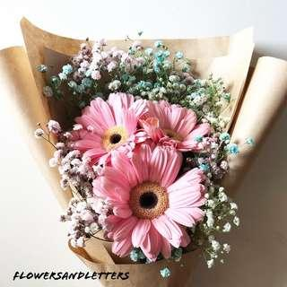 Valentine's Day Bouquet three stalks pink gerbera daisy wraps with mixed white, pink and blue baby's breath bouquet