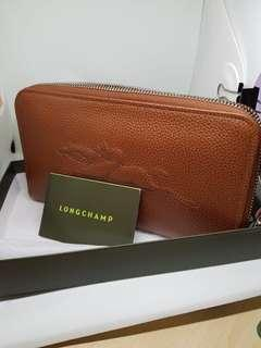 Authentic and New Longchamp unisex travel wallet with zipper. Brown leather.With Longchamp logo . Chic and elegant.