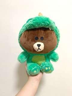 Brown bear in green dino costume
