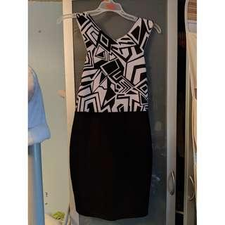 Medium bodycon dress. Black and white pattern on top with black skirt.