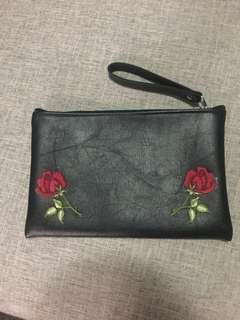 Black faux leather clutch with rose appliqués