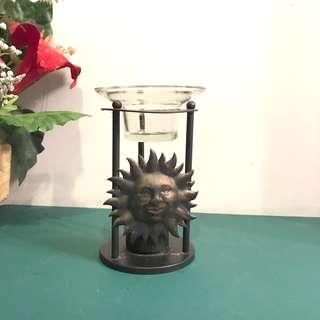 Glass candle holder on metal stand with sun design