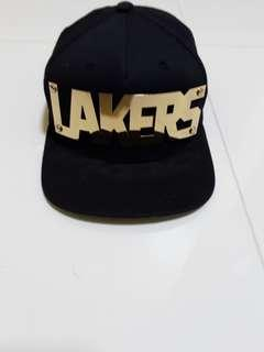Black cap with 'LAKERS' on it