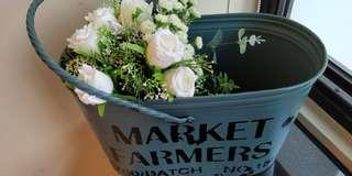Metal bucket with artifical flowers