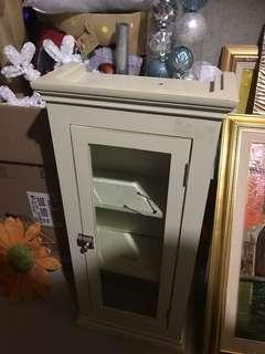 Cabinet with glass door you can use it in any room cream colour but can be painted can be hung or left on floor $75 OBO