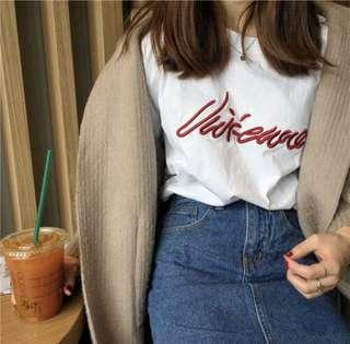 White top with red embroidered word