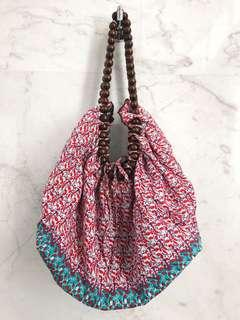 Slouched shoulder bag with wooden beaded handle.