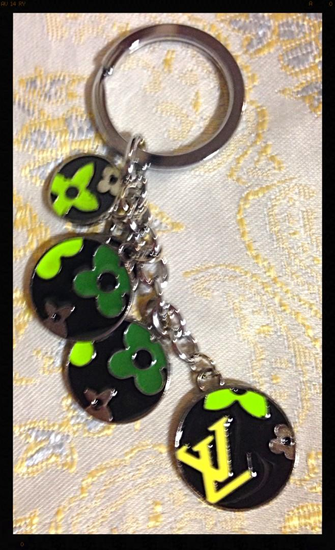 Great present! New LV logo keychain. Black background with green and yellow floral pattern.