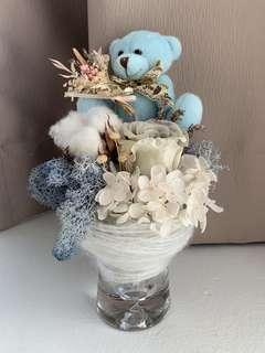 Dried blue rose bouquet in glass vase