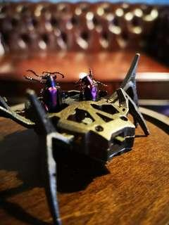 2 jewel beetle riding on a antique steampunk spider