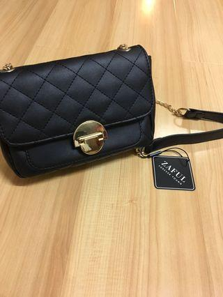 Small black bag with gold clasp