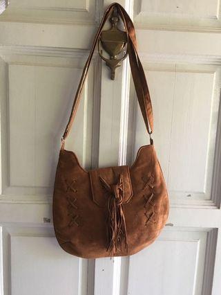 Suede brown tasseled handbag with adjustable straps.