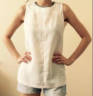 Sleeveless white top with crystal neckline