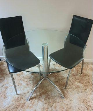 Round glass dining table with X 2 black chairs
