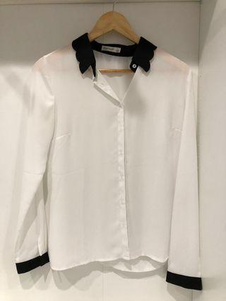 White blouse with black scalloped detail collar