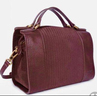 Burgundy bag with strap with tag attached