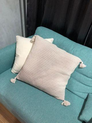 Knitted cushion cover with tassels
