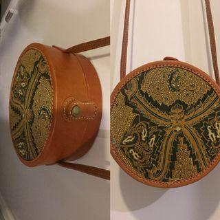 Round Batik Sling bag with real leather straps and button buckle.