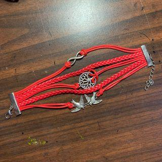 red friendship bracelet with charms