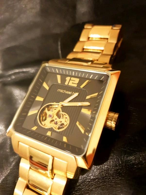 MICHAEL HILL MENS WINDING MECHANICAL GOLD STAINLESS STEEL WATCH.