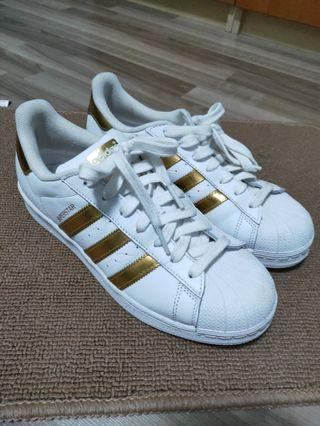 Adidas Superstar with gold stripes