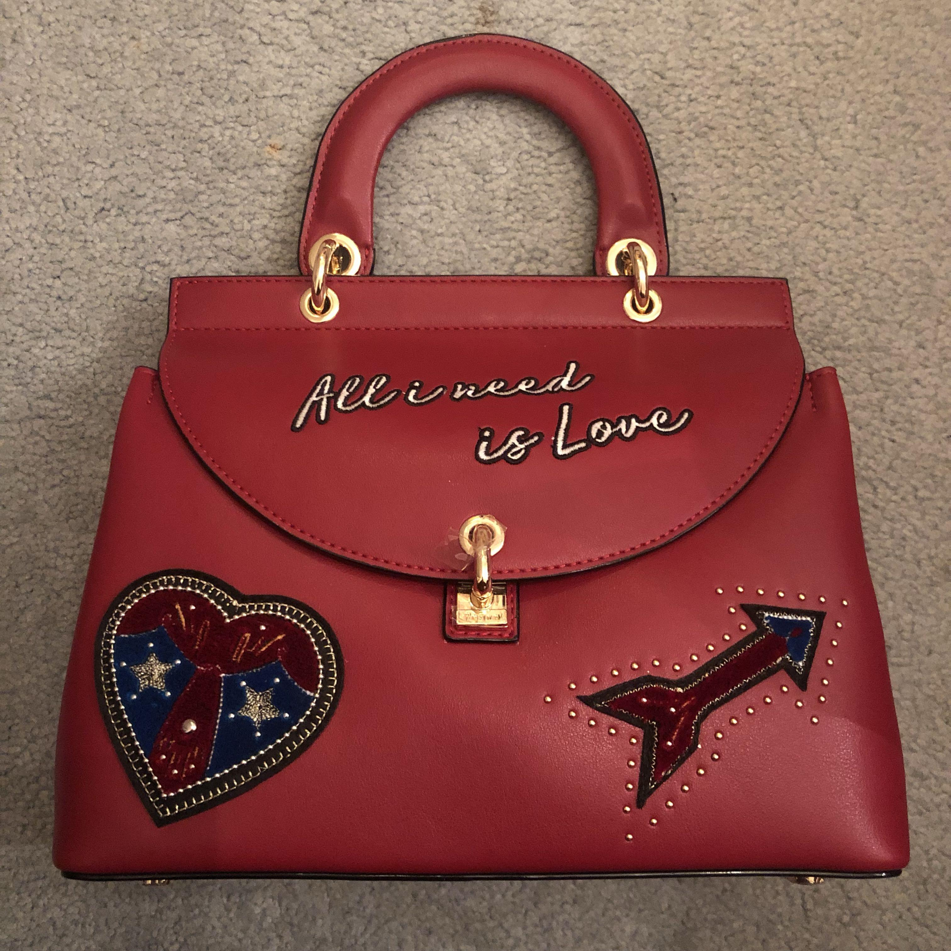 Red handbag with quote and stamps