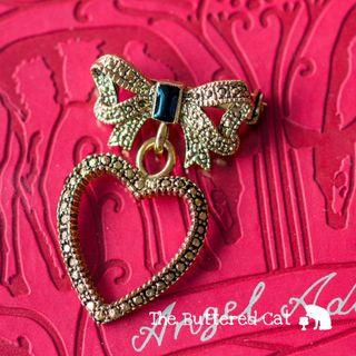Vintage bow brooch with a dangling heart shaped charm
