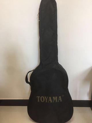 Acoustic guitar, with strings and a carry bag.