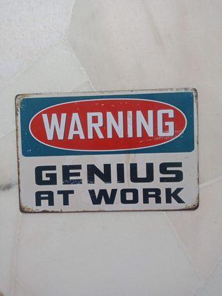 Warning Genius at Work sign