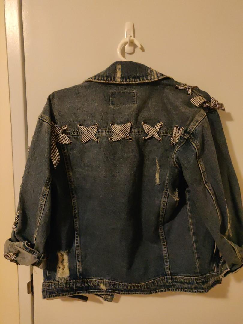 Denim jacket with ribbons weaved across the back