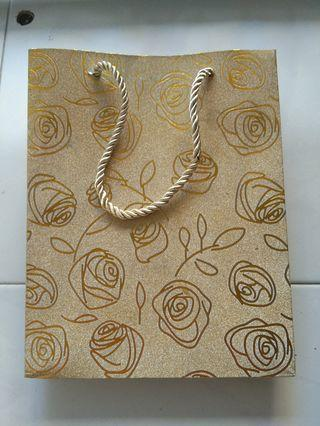 Gold colour paper bag with rose print