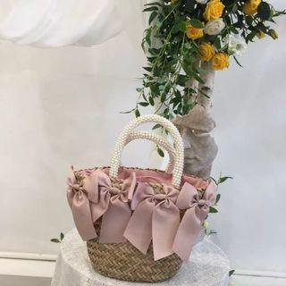 🚚 Straw bag with a sophisticated style pink ribbons at the front side and pink cloth interior white pearl handle