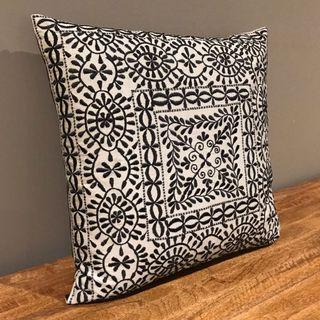 Silvery grey cushion with black embroidery pattern