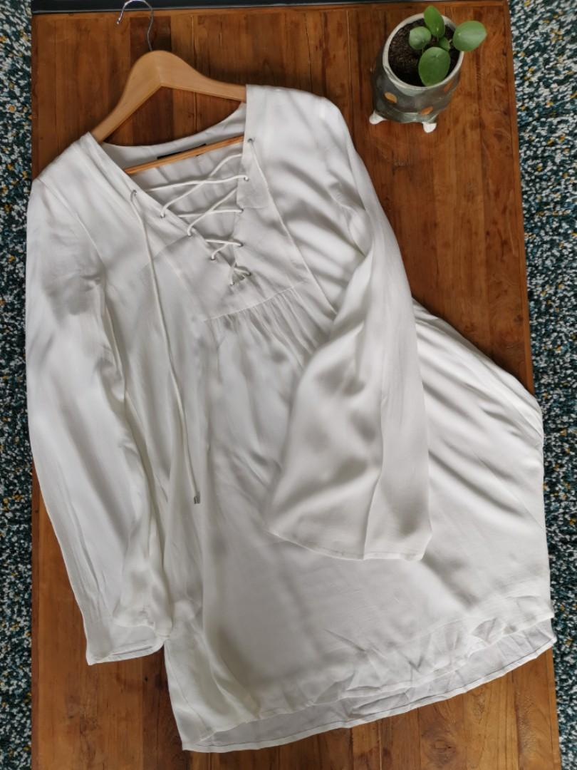 1970s style white dress with lace up front and bell sleeve