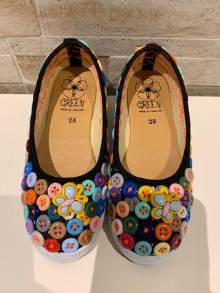 Colorful button sewed on shoe