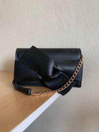 Call it Spring Crossbody sling bag in black bow