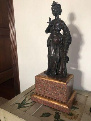 Brass lady statue on marble pedestal