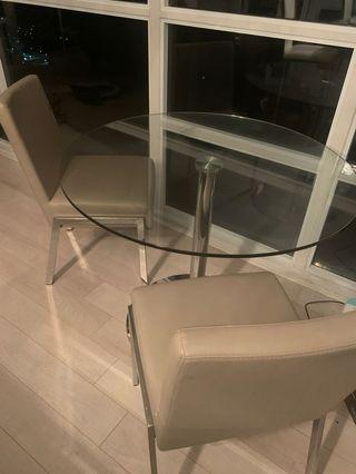 Round glass dining table with two leather seats