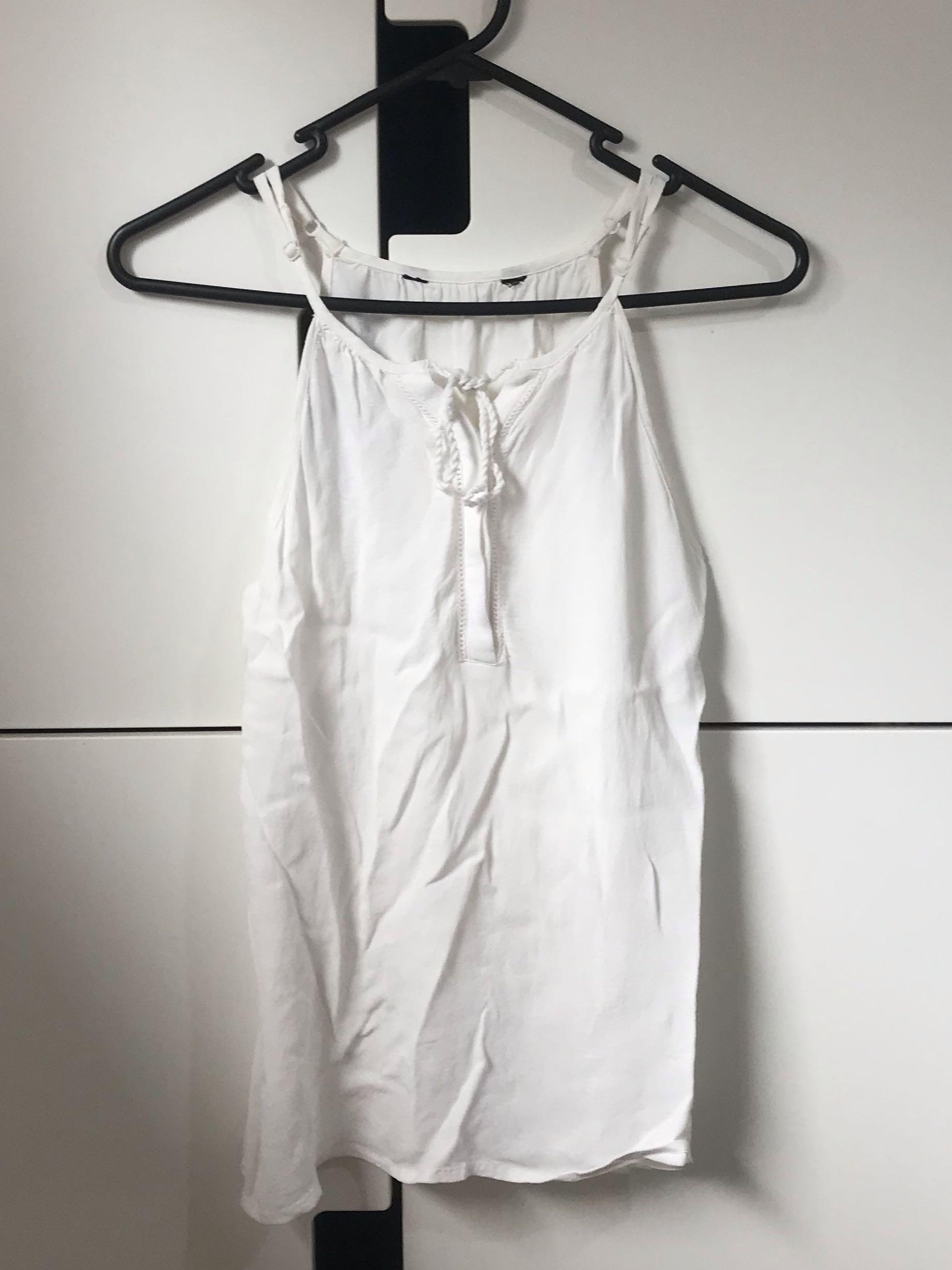 White sleeveless summer top with tassel details at the front