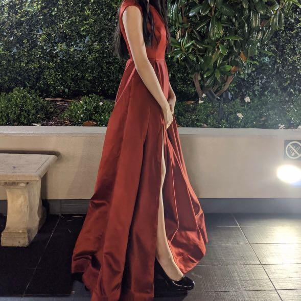 Deep red satin floor length a-line formal dress with capped sleeves, a wide neckline, with pockets and a leg slit