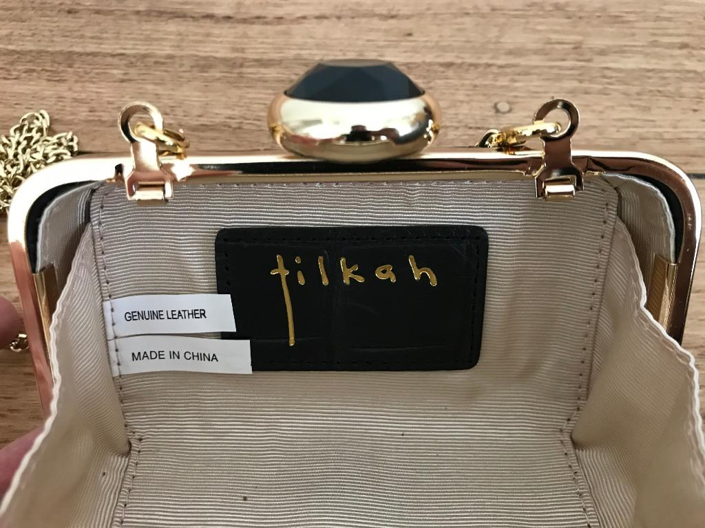 Tilkah black leather clutch with gold look trim and gold look chain.